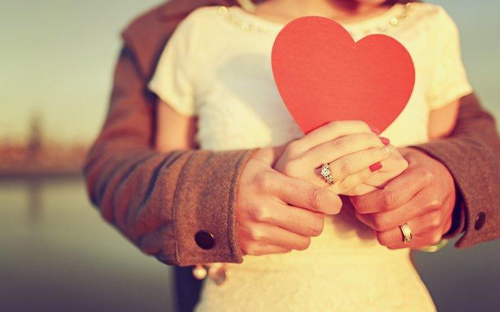 Супружеская пара с картонным сердцем в руках