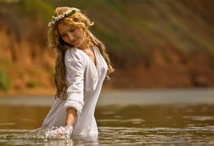 Девушка в венке проводит обряд у воды