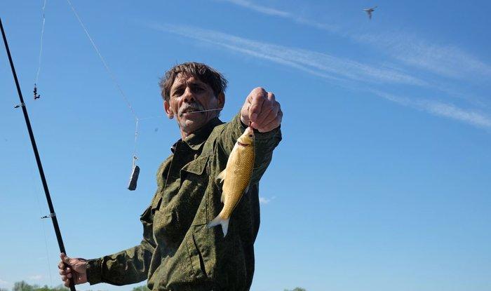 Мужчина хвастает пойманной рыбой