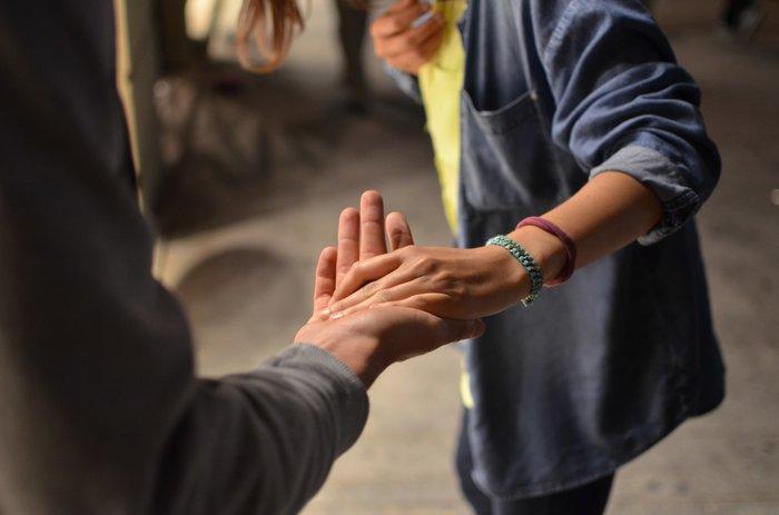 Пара расстается, держась за руки