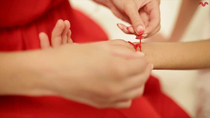 Завязывают красную нить на запястье