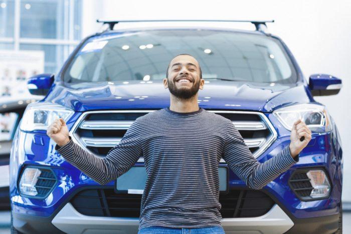 Мужчина радуется купленной синей машине