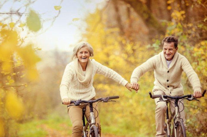Пожилая пара катается на велосипедах в парке