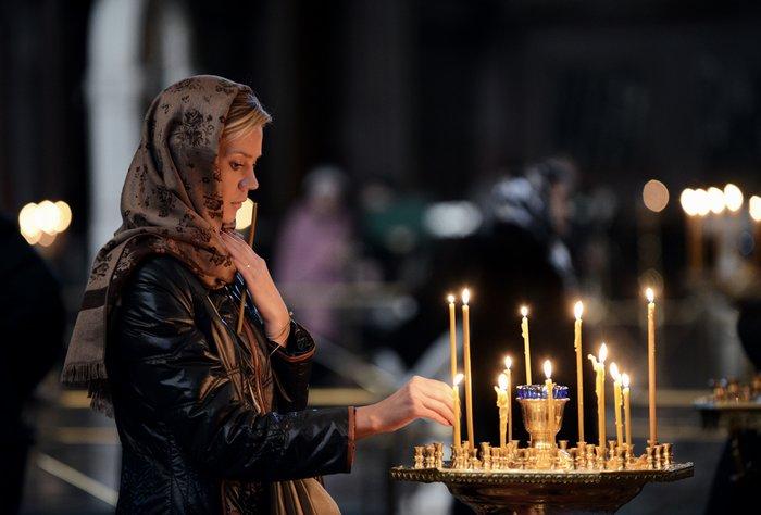 Женщина ставит свечку в церкви