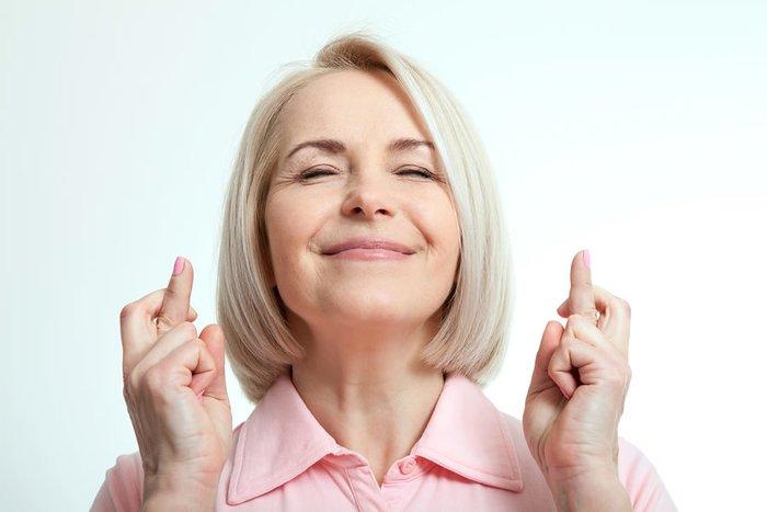 Женщина загадывает желание, скрестив пальцы