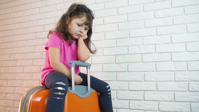 Грустная девочка сидит на чемодане