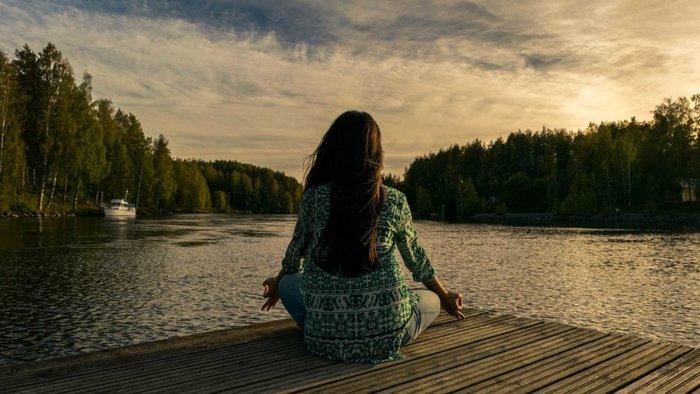 Женщина медитирует у воды
